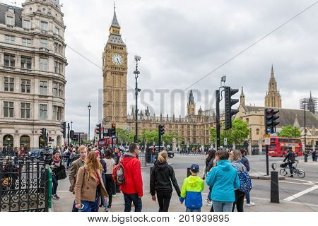 LONDON ENGLAND - JUNE 08 2017: Tourists and commuters at street crossing near Houses of Parliament in London UK