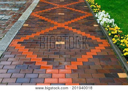 Beautiful pavement of red and brown clinker brick. Walking path decorated with flowers