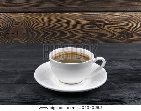 Overhead view of a freshly brewed mug of espresso coffee on rustic wooden background with woodgrain texture. Coffee break style concept