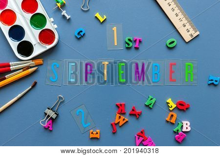 September 1st. Day 1 of month, Back to school concept. Calendar on teacher or student workplace background with school supplies on blue table. Autumn time.