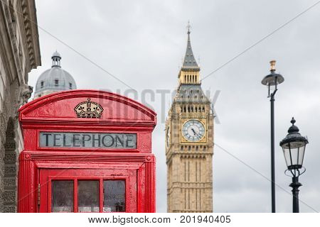 Red call box at Parliament square near Big Ben in London UK