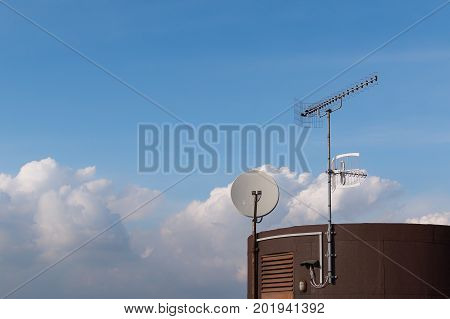 TV antenna and satelite dish mounted on roof. Against blue sky with clouds.