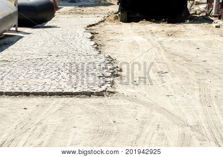 Cobble paving stone on the half of the street in the city reconstruction site