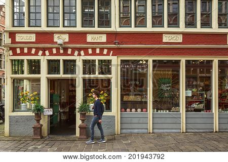 GHENT BELGIUM - JUNE 22 2016: Horizontal picture of a soap store with flowers a red top wall and a man walking by in downtown Ghent.