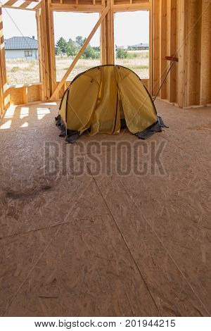 yellow tent pitched inside the built house being still without the roof
