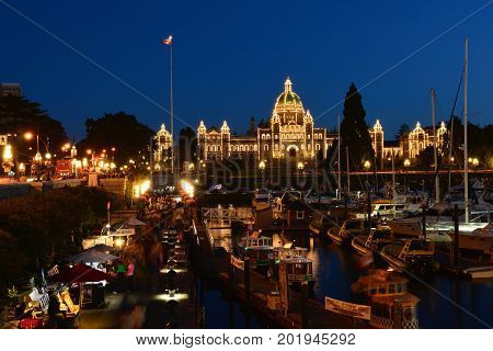Victoria BC,Canada,August 9th 2014.Victoria's busy inner harbor,parliament buildings,boats and many tourists enjoying the nightlife in Victoria.