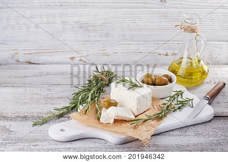 Fresh feta cheese with green olives olives oil and rosemary on white wooden serving board over light wooden background. Free space for text