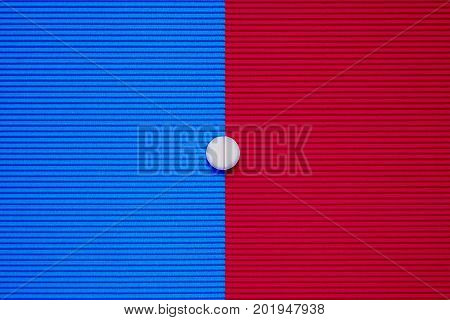 Medical tablet, pill on blue and red background.
