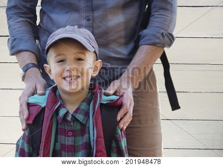 Digital composite of Father hands on son's shoulders against white wood panel