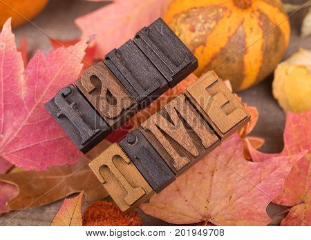 Wood letters spelling fall time on a colorful autumn background