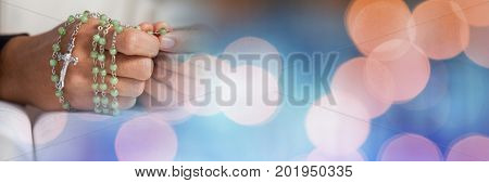 Digital composite of Hands with rosary on bible and blue orange bokeh transition