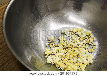 An empty metal popcorn bowl with only crumbs left
