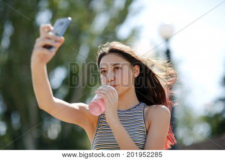 Close-up of a charming young lady in striped T-shirt taking a selfie with a refreshing pink beverage in a plastic cup on a natural blurred background. A fashion pretty girl makes a self-portrait.
