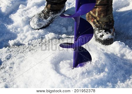 Drilling An Ice Fishing Hole With A Boots In The Background