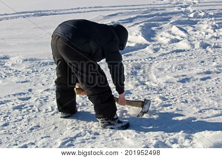 Chopping At An Old Ice Fishing Hole With An Axe