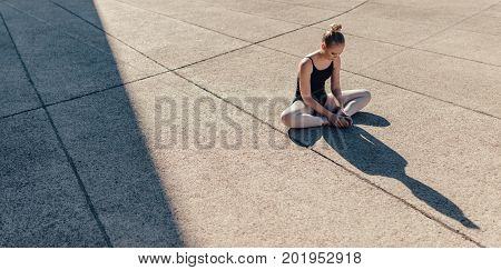 Ballet dancer stretching her legs before dance practice. Dancer sitting on floor joining both her feet.