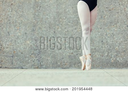 Closeup shot of legs of a female ballet dancer standing on her toes wearing pointe shoes. Ballet dancer practicing dance moves.