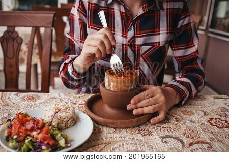 A restaurant visitor eats a national Turkish dish in a pot that is broken before being consumed called Testi-kebab.