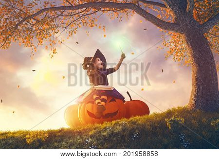 Happy Halloween! Cute cheerful little witch with a magic wand and book of spells. Beautiful child girl in costume sitting on the big pumpkin, conjuring and laughing.