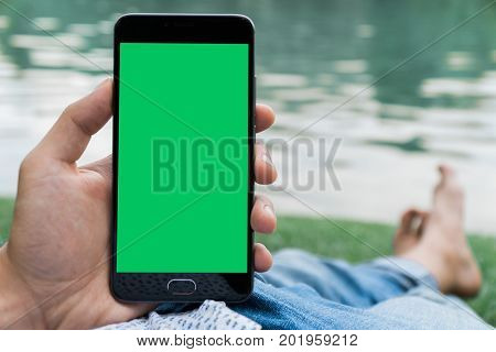 hand of man holding mobile smart phone with chroma key green screen on gren background