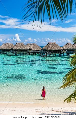 Luxury beach travel vacation woman in Tahiti. Tourist enjoying ocean water at overwater bungalow hotel villas in French Polynesia, Moorea island in south pacific, famous getaway destination.