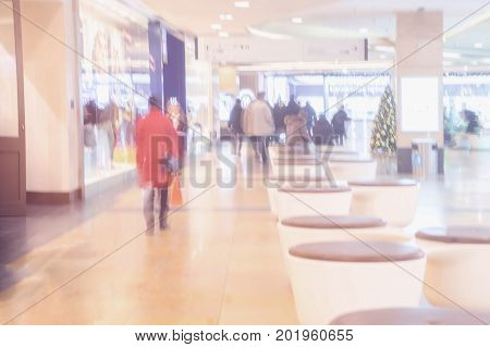 Abstract defocused motion blurred unrecognizable people people of different ages in the shopping center hurrying for gifts for loved ones in the pre-Christmas holidays. For background , backdrop