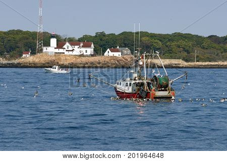 Fishing trawler by lighthouse coming home in Gloucester, Massachusetts. Gloucester is one of the oldest fishing ports in America.