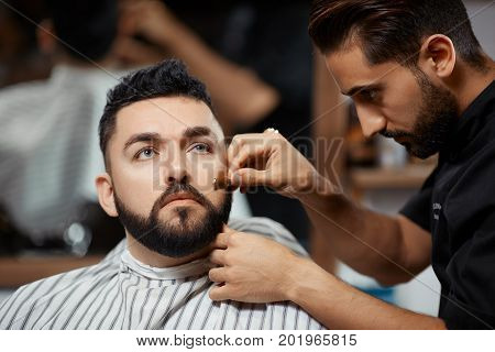 Handsome and carried man visiting barbershop for  correction bread and cutting hair. Brunet hairdresser working and cut hair with razor at modern barbershop for client.