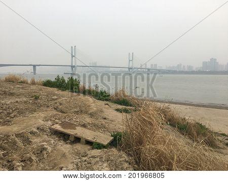 Yangtze river muddy riverbank and suspension bridge in Wuhan China