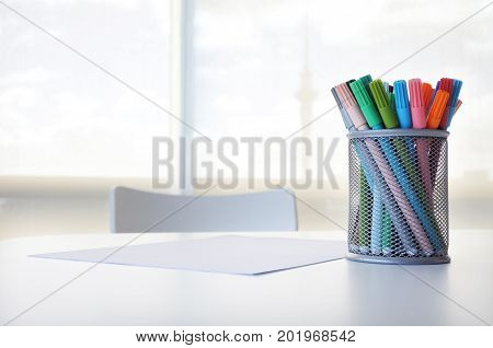 Colourful pens and blank white paper on a table with chair. Creativity concept. Copy space