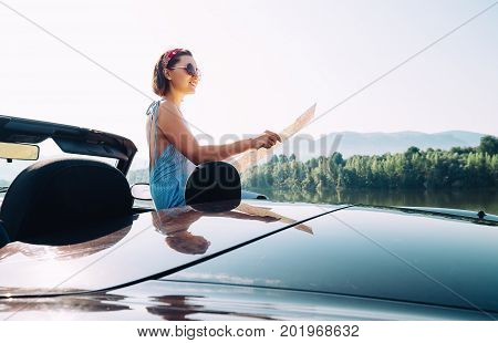 Young woman reads a roads map during auto travel