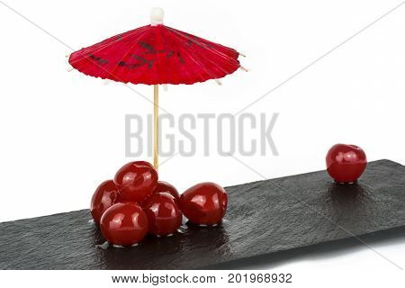 conceptual image loneliness isolation rejection and abandonment not fitting in showing a group of cherries together with one single cherry rejected. on a white background.