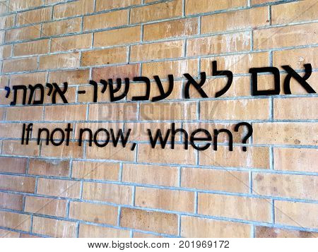 If not now when? Motivation moto quote in English and Hebrew written on a wall.