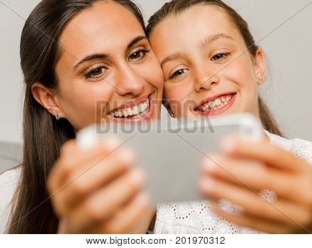 Beautiful Mom and Daughter at home, showing something on the phone