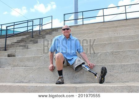 Man with prosthetic leg seated on concrete bleachers