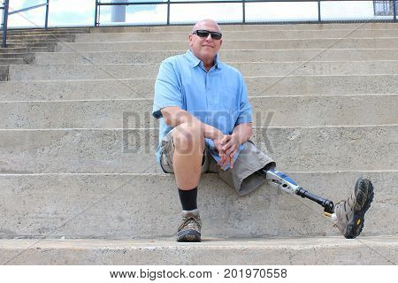 Seated man with prosthetic leg outstretched, on concrete bleachers