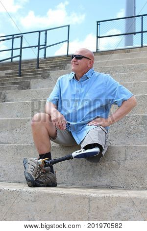 Amputee man seated with leg and prosthesis crossed, hand on hip