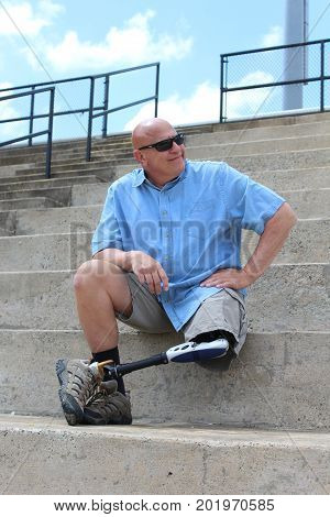 Amputee man seated with hand on hip and leg and prosthesis crossed