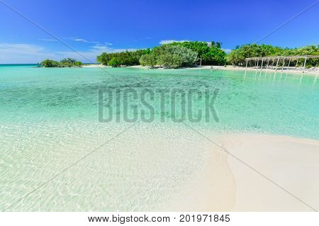 pretty amazing inviting view of tropical white sand beach and tranquil turquoise ocean lagoon on blue sky with fisherman in background at Cayo Coco Cuban island, sunny summer beautiful day