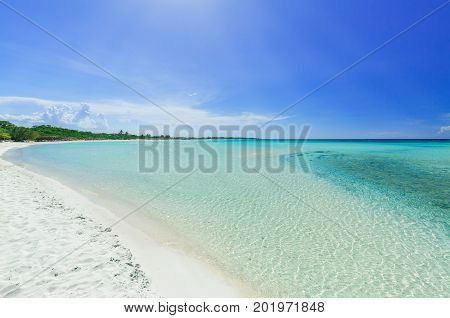 great amazing inviting view of tropical white sand beach and tranquil turquoise ocean on blue sky background at Cayo Coco Cuban island, sunny summer beautiful day