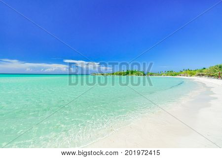 nice amazing inviting view of tropical white sand beach and tranquil turquoise ocean on blue sky with people in background at Cayo Coco Cuban island, sunny summer beautiful day