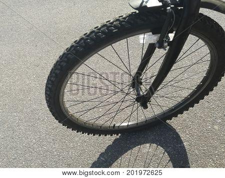 Close up of front bike wheel on asphalt