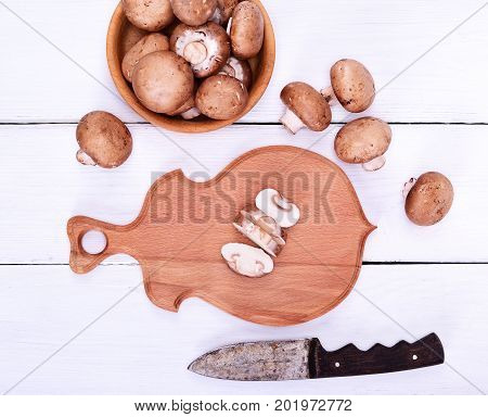 Fresh mushrooms champignons on a wooden cutting board top view