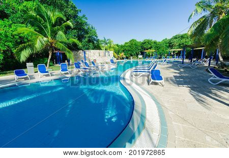 Cayo Coco island, Cuba, Iberostar Mojito resort, July 17, 2017, beautiful, amazing inviting view of a swimming pool in tropical garden with people relaxing in background lit by a sun rays