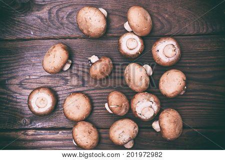 Fresh mushrooms champignons on a brown wooden background