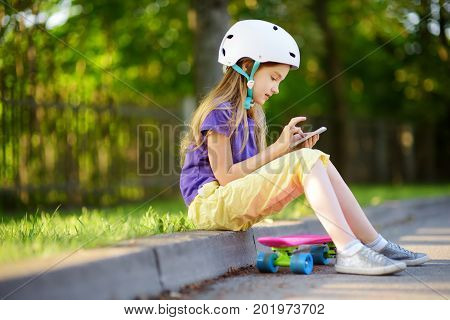 Pretty Little Girl Learning To Skateboard On Beautiful Summer Day In A Park. Child Enjoying Skateboa