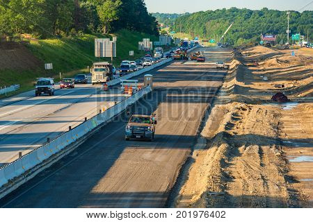 BEDFORD HEIGHTS OH - JUNE 28 2017: Crews begin the work of adding new lanes to the median of I-271 near Cleveland while morning traffic backs up.