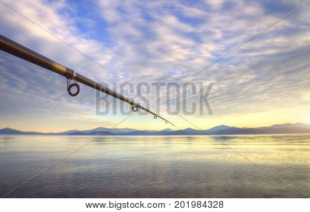 spinning - fishing rod on the summer lake at sunset