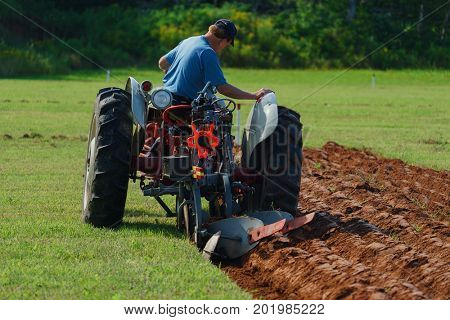 DUNDAS, PRINCE EDWARD ISLAND, CANADA - 25 Aug: Competitor plow with antique tractor at the PEI Plowing Match and Agricultural fair on August 25, 2017 in Dundas, Prince Edward Island.