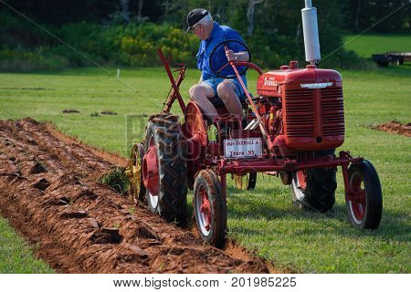 DUNDAS, PRINCE EDWARD ISLAND, CANADA - 25 Aug: Competitor plows with antique tractor at the PEI Plowing Match and Agricultural fair on August 25, 2017 in Dundas, Prince Edward Island.